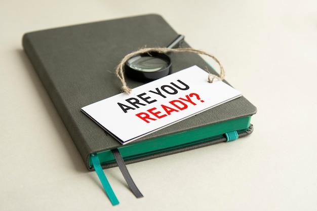 No caderno cinza está uma lupa e um cartão de papel branco com a inscrição está pronto, foco seletivo