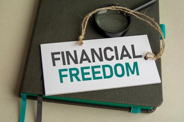 No caderno cinza está uma lupa e um cartão de papel branco com a inscrição liberdade financeira, foco seletivo
