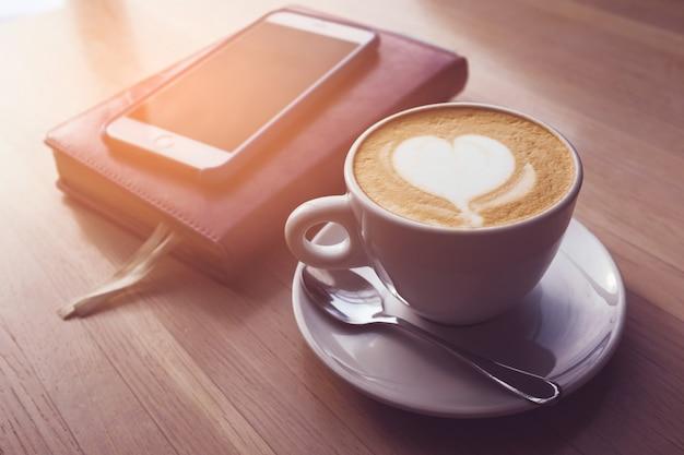 No café em uma mesa de madeira é uma xícara de capuccino, laptop, telefone, notebook, diário.