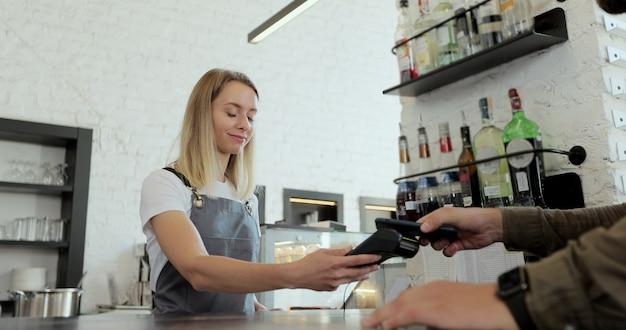 No café, uma mulher prepara café para viagem para um cliente que paga pelo celular sem contato para o sistema de cartão de crédito.