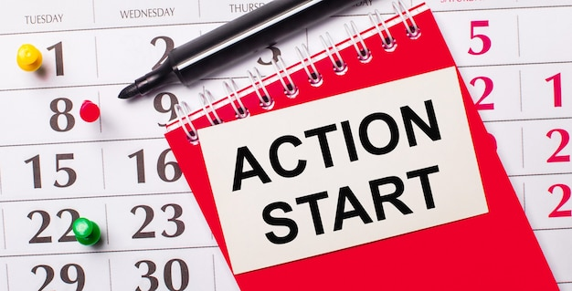 No calendário está um cartão branco com o texto início de ação. perto está um bloco de notas vermelho e um marcador. vista de cima