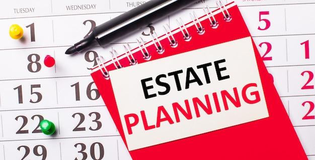 No calendário, há um cartão branco com o texto planejamento de imóveis. perto está um bloco de notas vermelho e um marcador. vista de cima