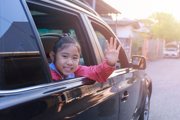 No caminho para a escola, a menina estendeu a mão da janela do carro, rindo e sorrindo.