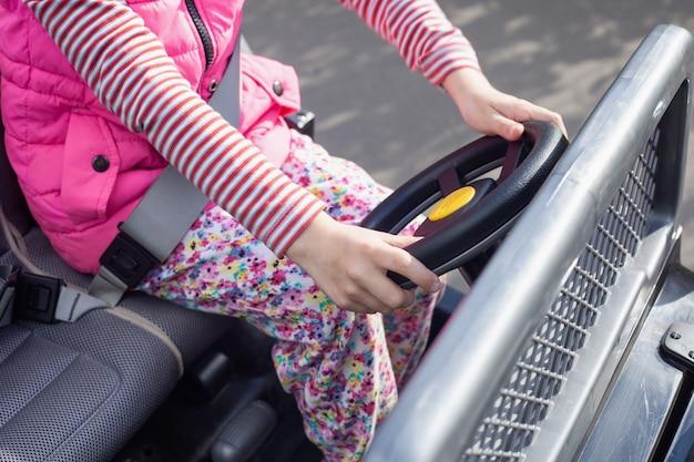 No carro elétrico, senta-se uma garota de fivela e segura o volante.