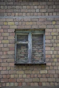 No centro da parede de tijolos há uma janela antiga totalmente revestida de tijolos, murada com tijolos e cimento