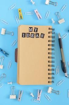 No centro, encontra-se um caderno aberto sobre molas com páginas marrons.
