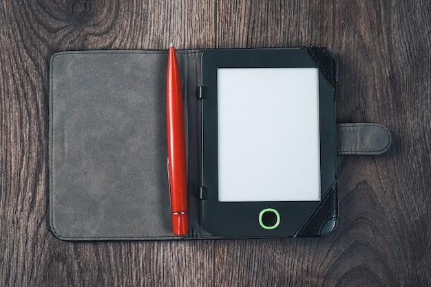 No chão de madeira escura está um livro eletrônico e uma caneta vermelha