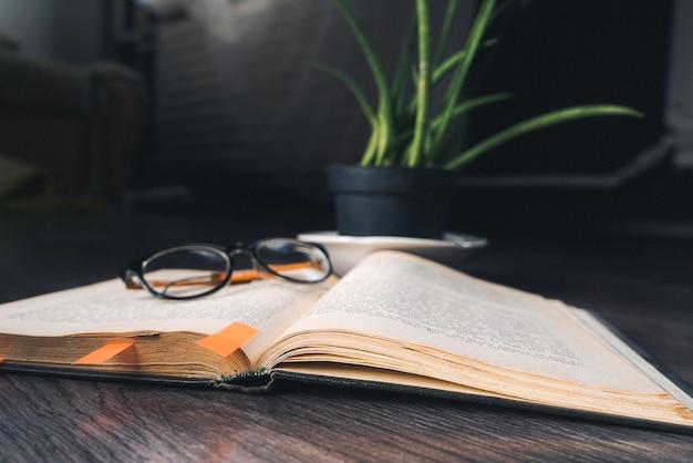 No chão de madeira está um livro e copos, uma planta verde em um vaso