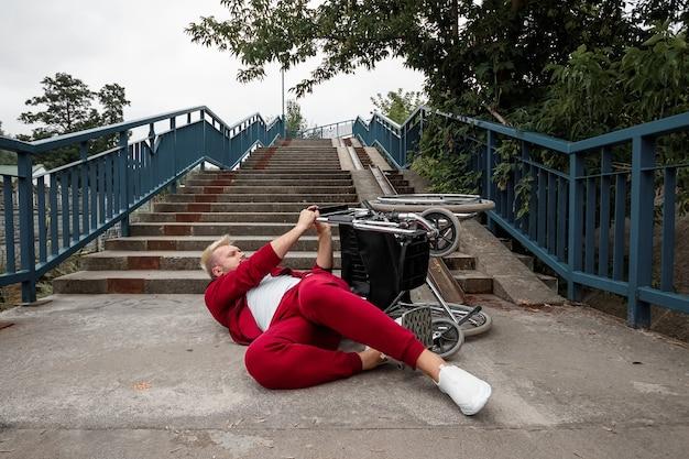 No chão perto da escada está um homem deficiente perto da cadeira de rodas. o conceito de cadeira de rodas, pessoa com deficiência, vida plena, paralítica, pessoa com deficiência.