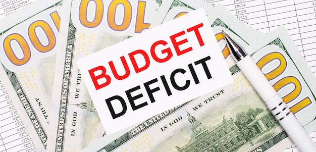 No contexto de relatórios e dólares - uma caneta branca e um cartão com o texto deficit orçamental. conceito de negócios