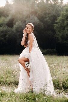 No dia do casamento, uma noiva elegante em um vestido longo branco e luvas com um buquê nas mãos está em uma clareira curtindo a natureza. bielo-rússia.