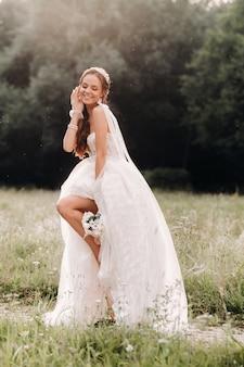 No dia do casamento, uma noiva elegante em um vestido longo branco e luvas com um buquê nas mãos