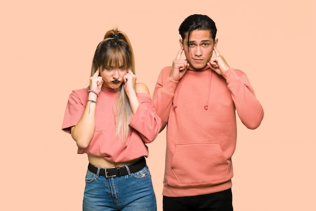 No dia dos namorados casal jovem cobrindo ambas as orelhas com as mãos sobre fundo rosa