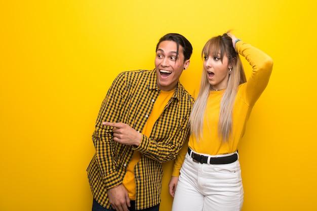 No dia dos namorados casal jovem sobre fundo amarelo vibrante, apontando o dedo para o lado e apresentando um produto