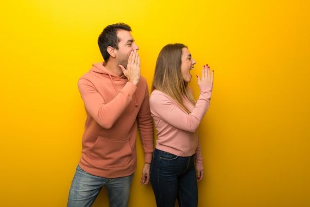 No dia dos namorados grupo de duas pessoas em fundo amarelo gritando com a boca aberta para o lateral