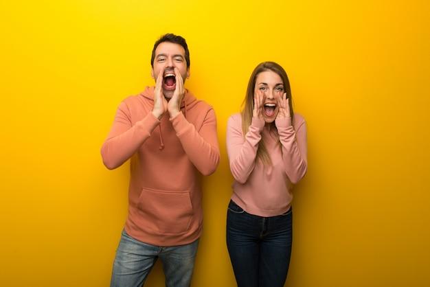 No dia dos namorados grupo de duas pessoas em fundo amarelo gritando e anunciando algo