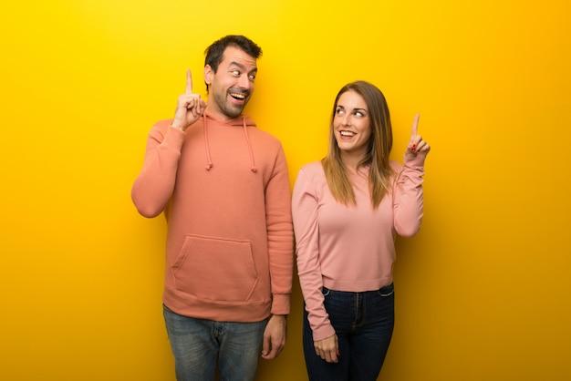 No dia dos namorados grupo de duas pessoas no fundo amarelo com a intenção de perceber a solução, enquanto levanta um dedo para cima