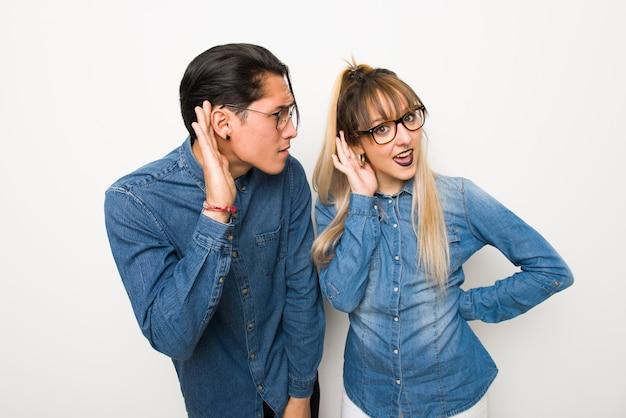 No dia dos namorados jovem casal com óculos, ouvindo algo, colocando a mão sobre a orelha