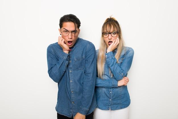 No dia dos namorados jovem casal com óculos surpreso e chocado ao olhar para a direita