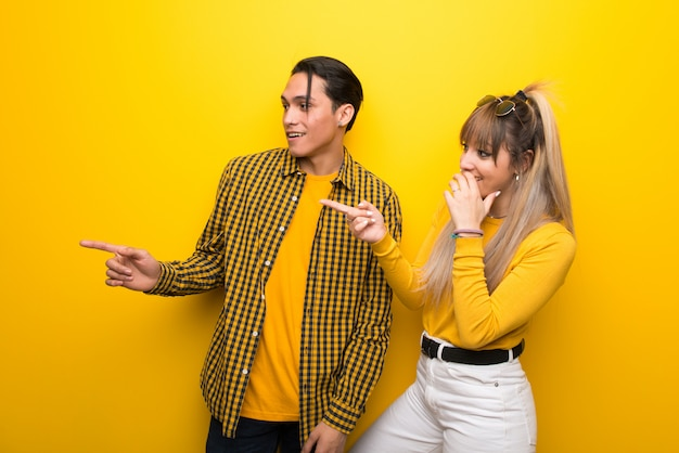 No dia dos namorados jovem casal sobre fundo amarelo vibrante, apontando o dedo para o lado com uma cara de surpresa