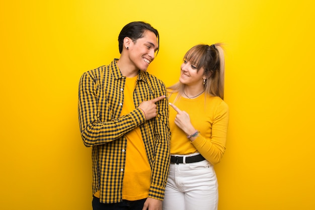No dia dos namorados jovem casal sobre fundo amarelo vibrante, apontando para o lado para apresentar um produto