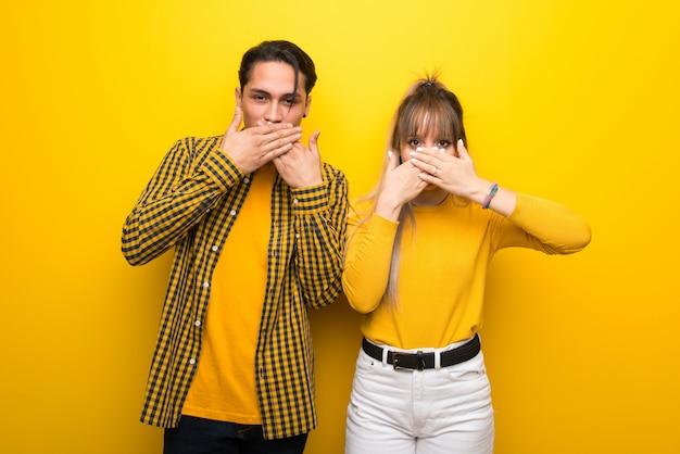 No dia dos namorados jovem casal sobre fundo amarelo vibrante cobrindo a boca com as mãos para dizer algo inadequado