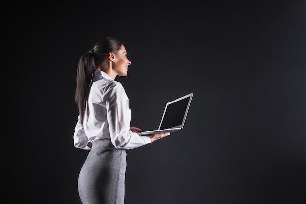 No escritório. mulher de negócios alegre e feliz segurando um laptop e olhando para a tela do computador enquanto sorri