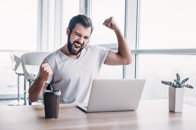 No escritório, o empresário sentado à mesa, usando o laptop, termina o projeto e ganha muito. faz gestos bem-sucedidos, levanta os braços em comemoração. sua xícara de café está na frente dele