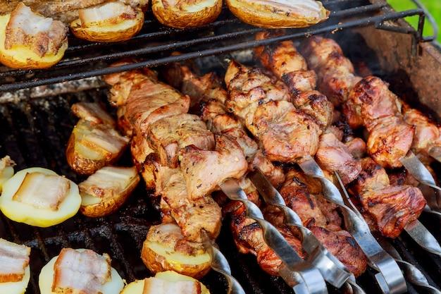No espeto cru que grelha no espeto do metal. carne assando no churrasco com legumes.