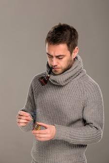 No estúdio, sobre um fundo cinza, um homem de suéter cinza fica pensativo, acende um fósforo para acender um cachimbo que ele segura na boca.