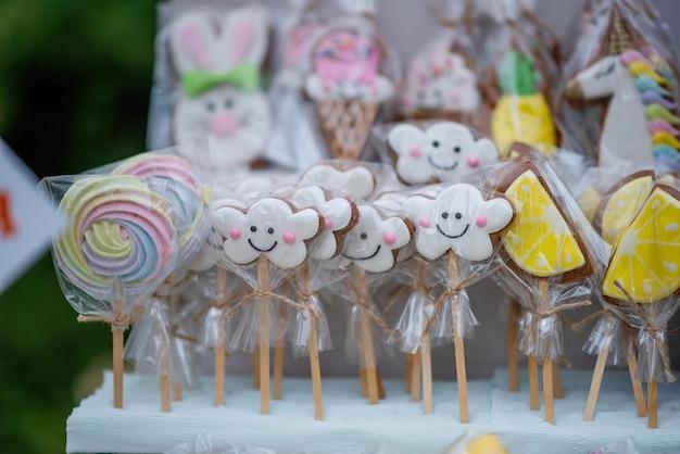 No festival de comida de rua, há biscoitos de gengibre em uma embalagem de celofane na forma de nuvens, pôneis, arco-íris, limões no balcão. cumprimento da higiene, saneamento no feriado