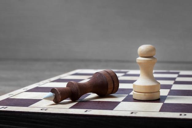 No final do jogo de xadrez, o peão branco derrotou o rei escuro. espaço da cópia do conceito de negócio, foco seletivo.