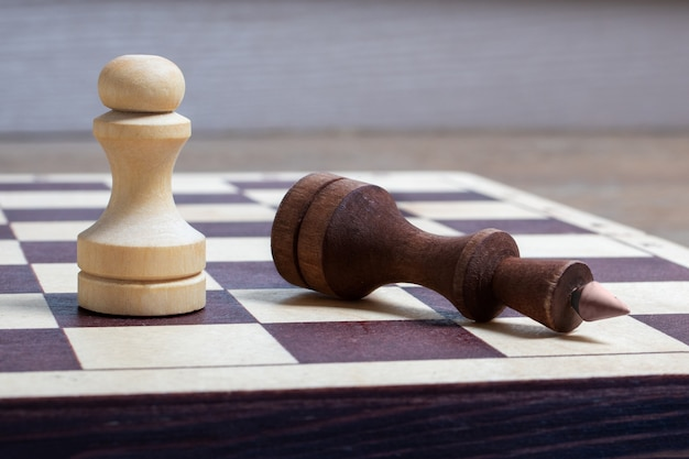 No final do jogo de xadrez, o peão branco derrotou o rei escuro. o rei do xadrez caído como metáfora da queda do poder. espaço de cópia de conceito de negócio, foco seletivo