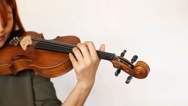 No foco seletivo da mão de uma mulher segurando e pressionando o dedo na corda, mostre como tocar instrumento acústico, luz embaçada ao redor
