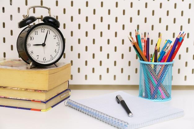 No fundo branco da mesa há um despertador preto que guarda um caderno, uma caneta e um lápis ...