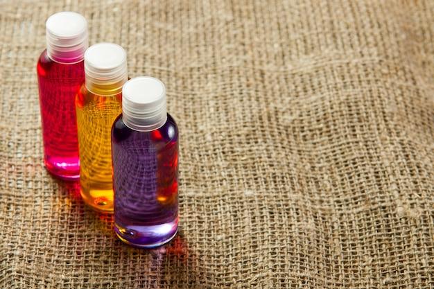 No fundo de um suporte de tecido de linho, os frascos com meios cosméticos