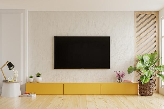 No fundo de uma parede de gesso, uma tv é montada em um gabinete amarelo