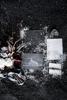 No fundo preto encontram-se alianças de casamento, cartões cinza e brancos, um buquê de flores e fitas coloridas