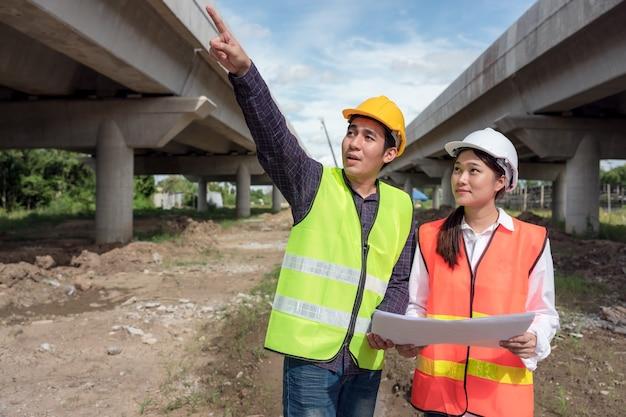 No fundo, quadros de formas de concreto arranha-céus e um retrato de uma trabalhadora confiante em uma construção.