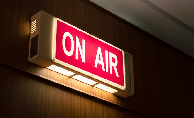 No ícone de sinal de ar brilhando na parede de madeira da sala de produção de rádio de transmissão ao vivo