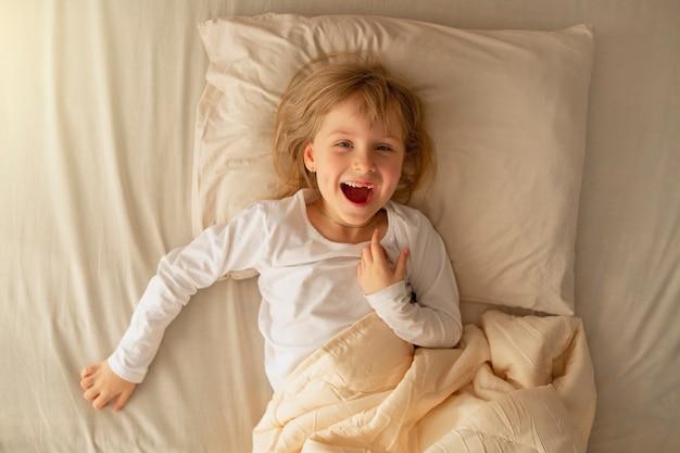 No início da manhã, a pré-escolar deita-se na cama e se diverte depois de um bom sono saudável
