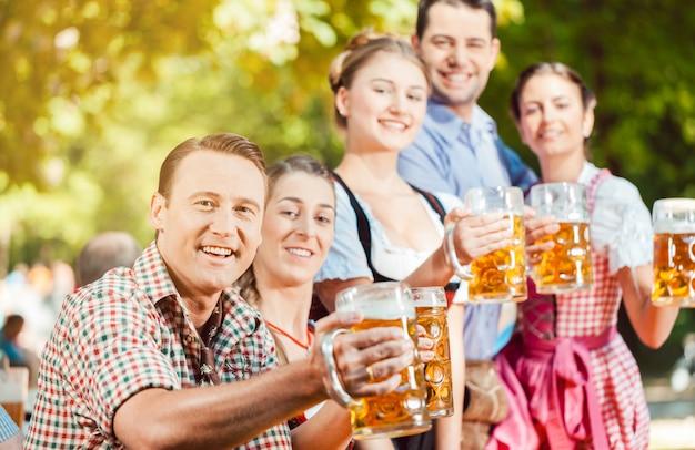 No jardim da cerveja - amigos bebendo cerveja na baviera na oktoberfest