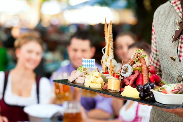 No jardim da cerveja - amigos em uma mesa com cerveja