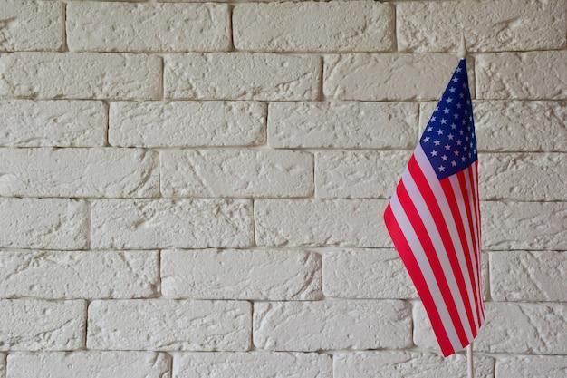 No lado direito da moldura está a bandeira dos eua contra o fundo de uma parede de tijolos
