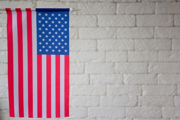 No lado esquerdo do quadro está a bandeira dos eua contra o fundo de uma parede de tijolos blured