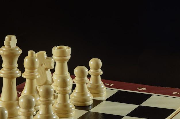 No lado esquerdo do tabuleiro estão diferentes peças de xadrez de madeira. o tabuleiro de xadrez encontra-se obliquamente