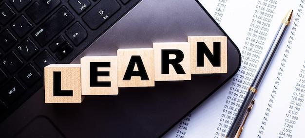 No laptop, em cubos de madeira perto da caneta, está escrita a palavra aprender.