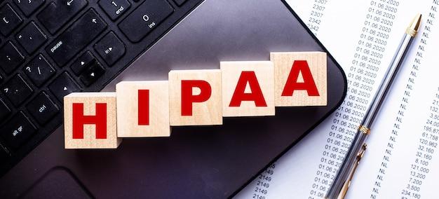No laptop, em cubos de madeira perto da caneta, está escrita a palavra hipaa.