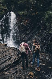 No lugar incrível. retrovisor de corpo inteiro de um jovem casal de mãos dadas perto da cachoeira