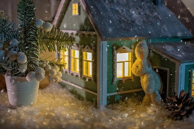 No meio da paisagem de inverno, um coelhinho de brinquedo espia pela janela de uma casa de aldeia perto de uma árvore de natal.